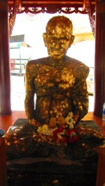 Gold leaf pressings on a statue of Buddha, marking prayers given. His forehead, cheeks, lips and heart are covered in layers of gold.